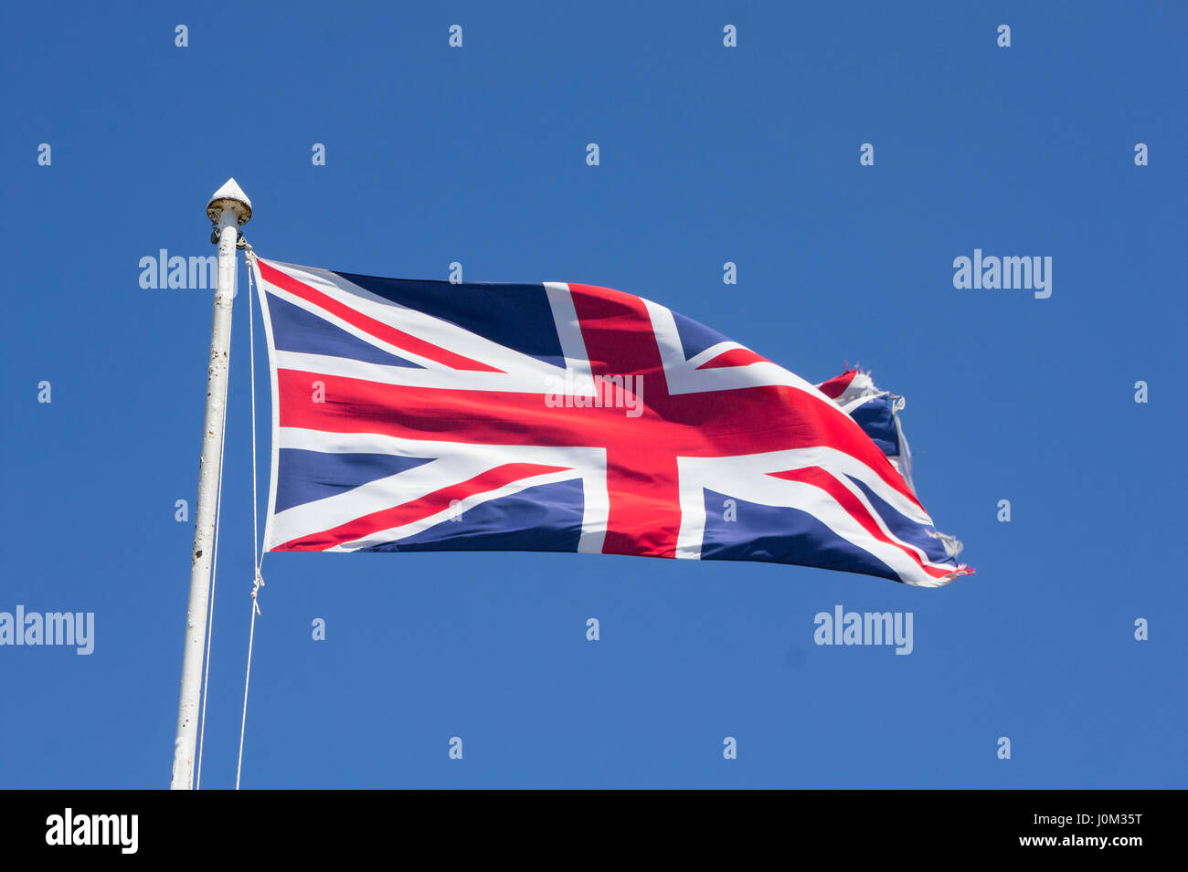 United Kingdom flag waving against blue sky from an old flagpole - Stock Image