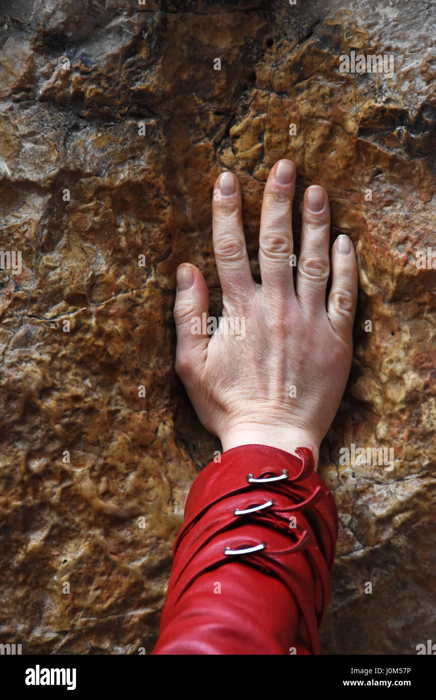 A pilgrim blesses a cross with Jesus hand print, in Via Dolorosa station 5, Stock Photo