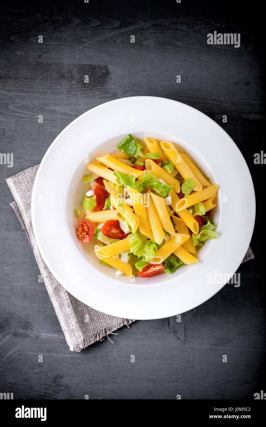 Pasta salad with fresh greenery and tomatos. - Stock Image