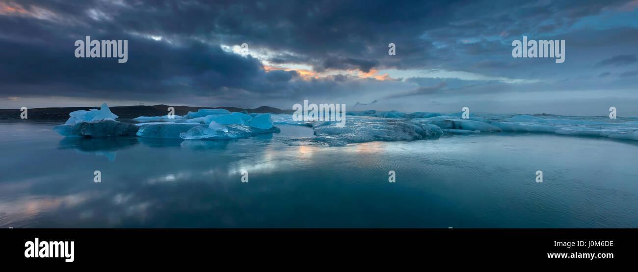 Floating ice in Jokulsarlon lagoon under the setting sun - Stock Image