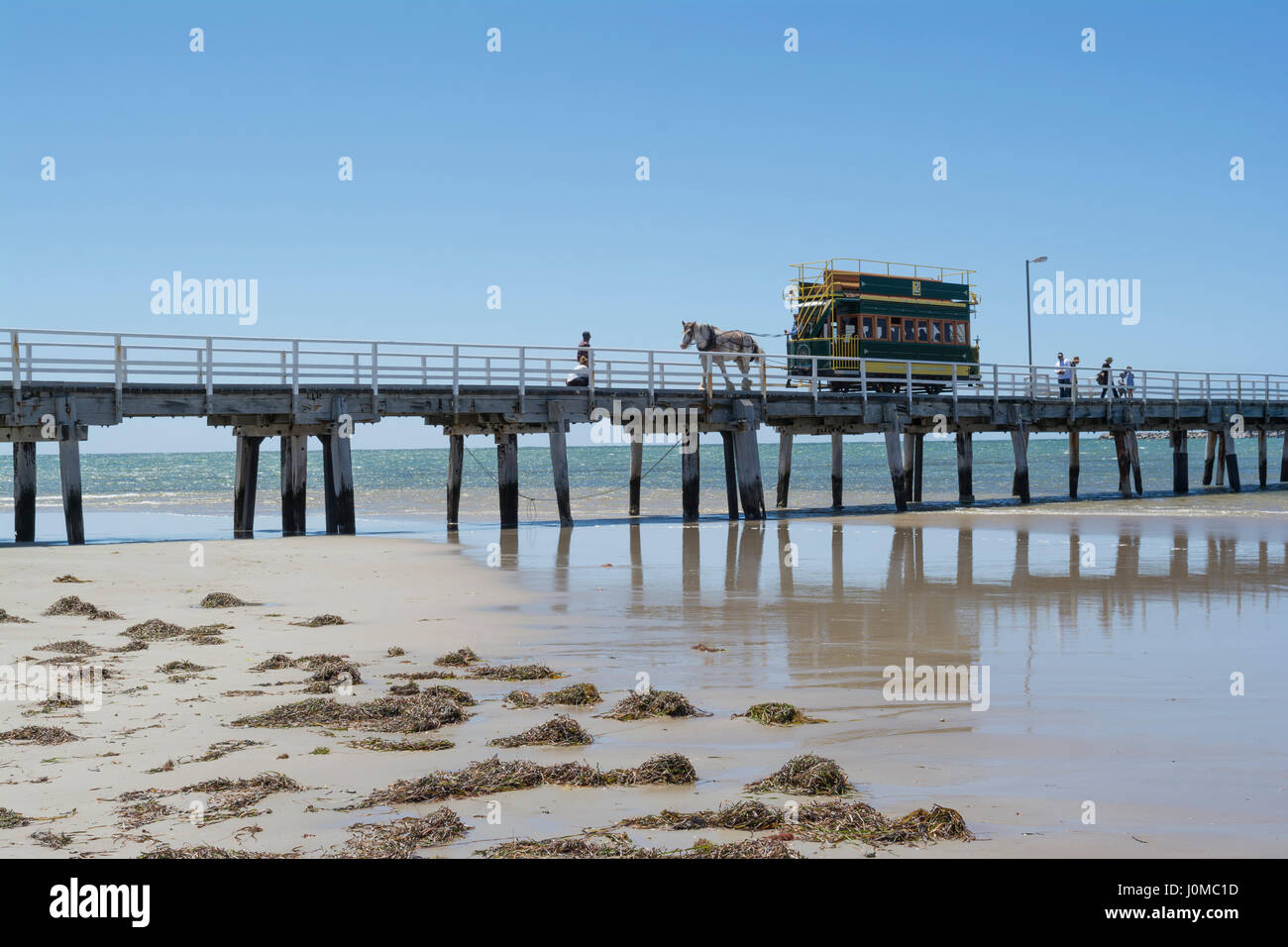 Victor Harbor, SA, Australia - Dec 20, 2016: Horse Drawn Tram filled with tourists travelling along the bridge from - Stock Image
