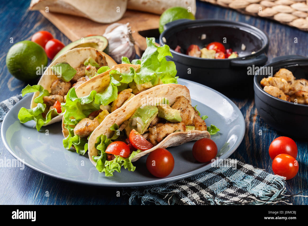Authentic mexican tacos with chicken and salsa with avocado, tomatoes and chillies. Mexican cuisine. - Stock Image