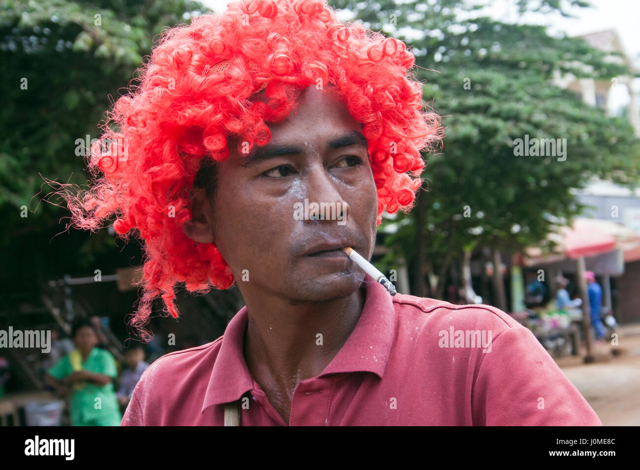 A Cambodian man is smoking a cigarette while wearing a red wig as he celebraties Khmer New Year in Chork Village, Stock Photo
