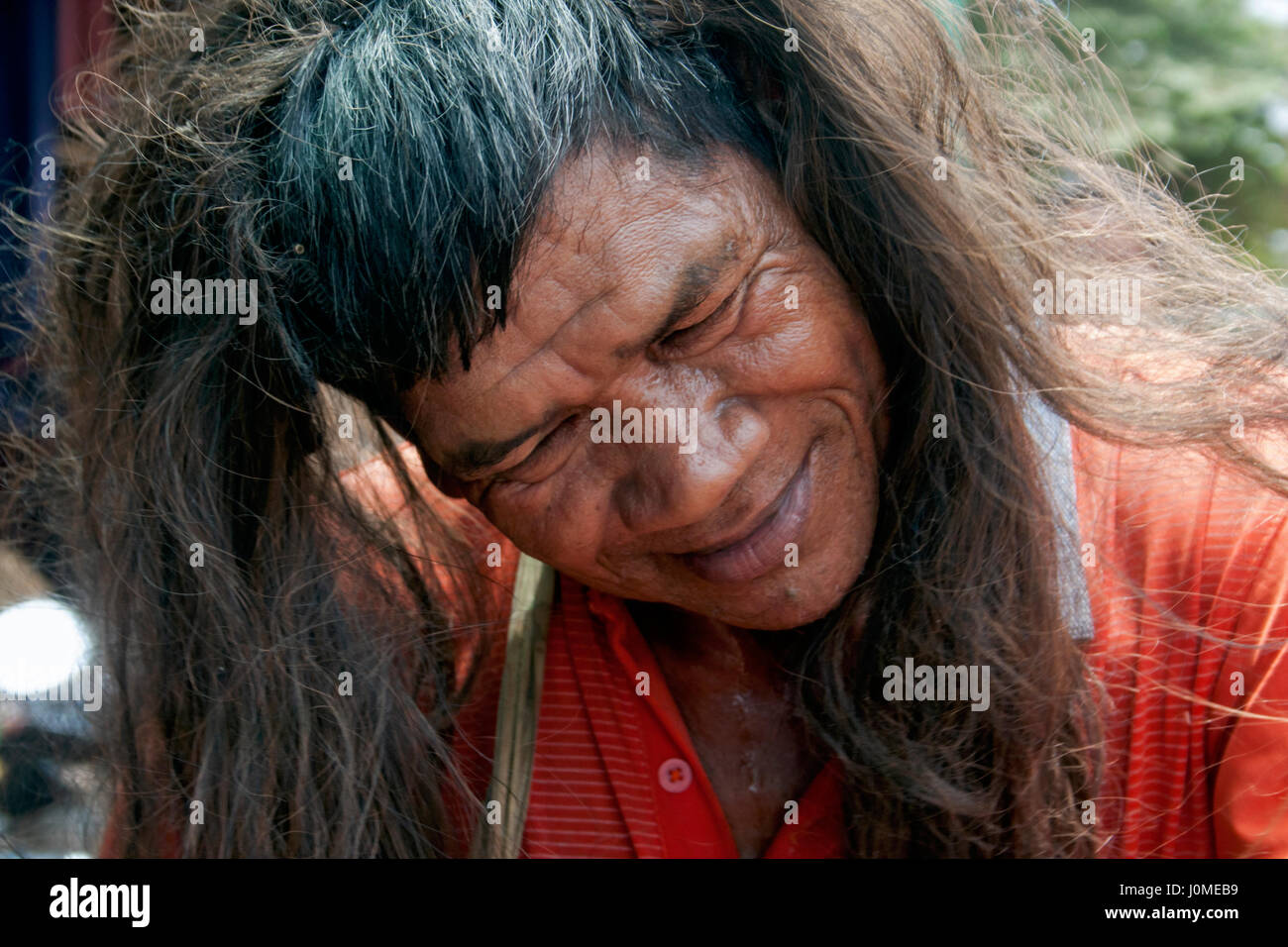 A Cambodian man is wearing a wig while celebrating Khmer New Year in Chork Village, Tboung Province, Cambodia. Stock Photo
