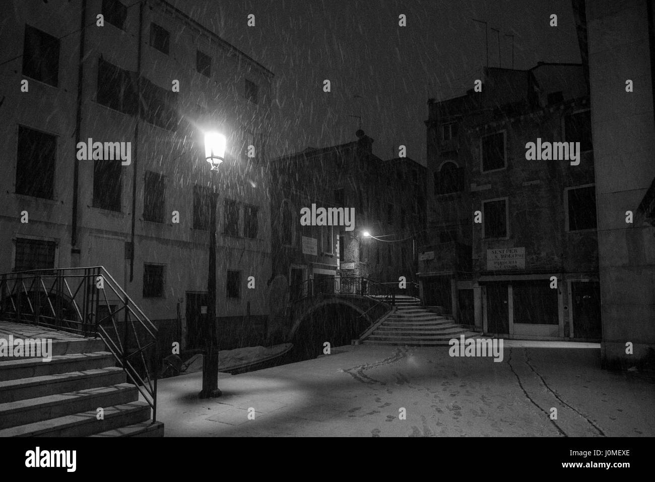 A bridge and a canal completely white during an heavy snow in Venice. - Stock Image