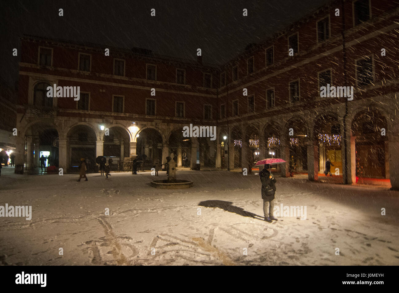 A woman poses during an heavy snow fall in Venice. - Stock Image