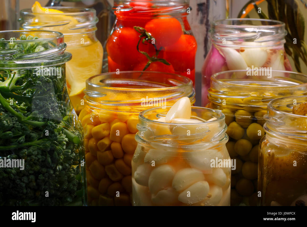 Opened jars in pantry with various preserved food Stock Photo