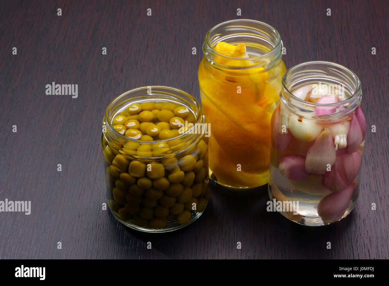 Three opened jars with green peas, onions and lemons on dark board. Copy space on left. - Stock Image