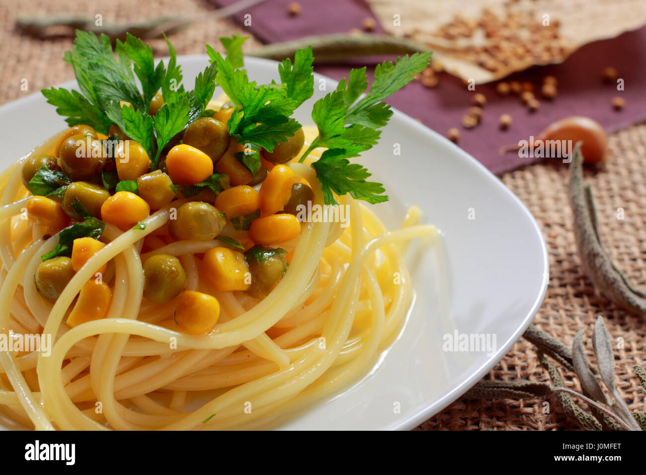 Spaghetti with green peas (preserved), sweetcorn and parsley leaves on plate - Stock Image