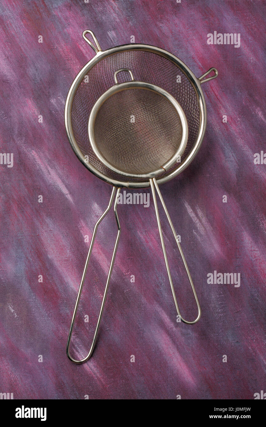 Pair of empty kitchen sieves over painted textile background. Overhead view. - Stock Image
