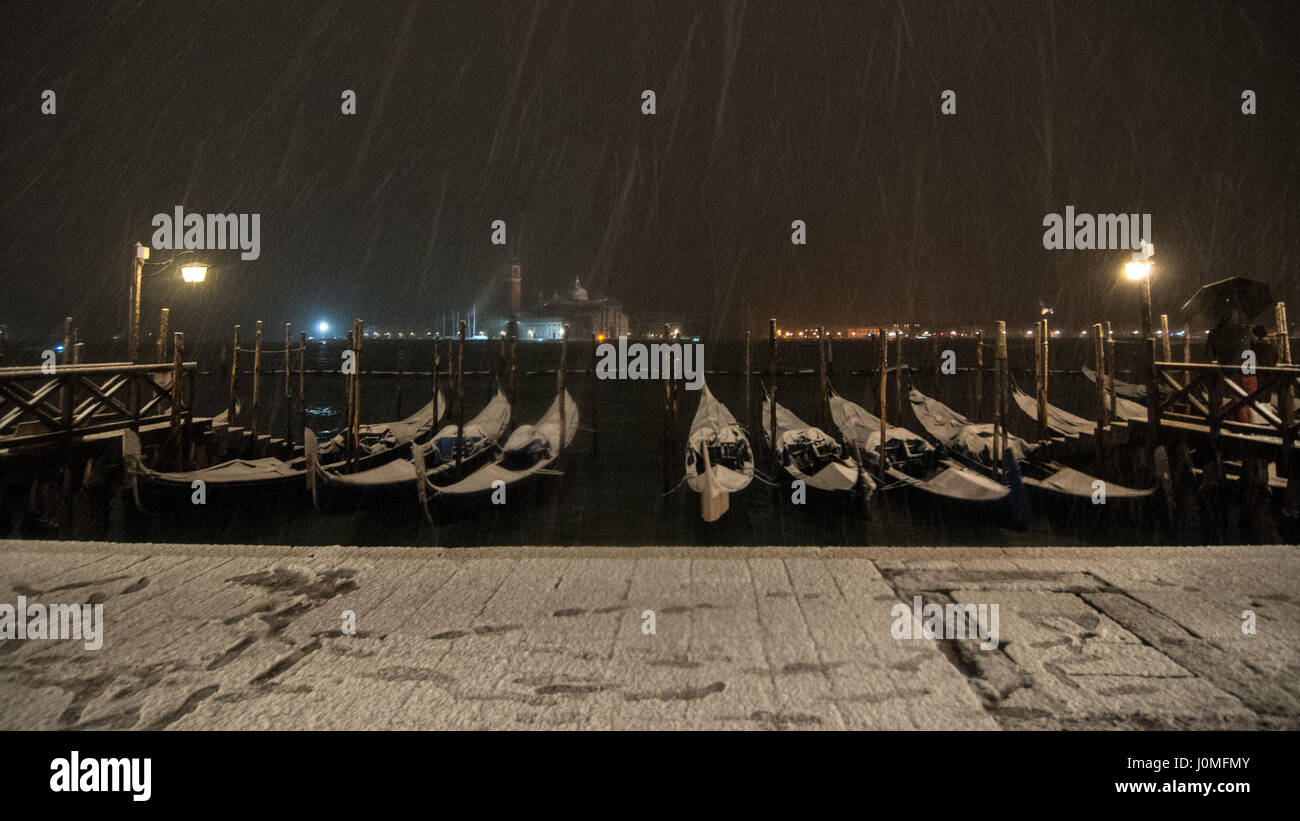 Gondolas during an heavy snow fall in Venice. - Stock Image