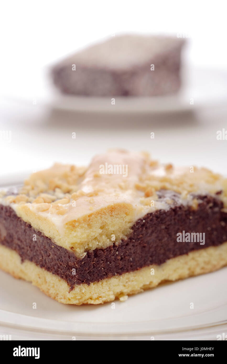 Close-up of cake on a plate with second piece on the background. - Stock Image