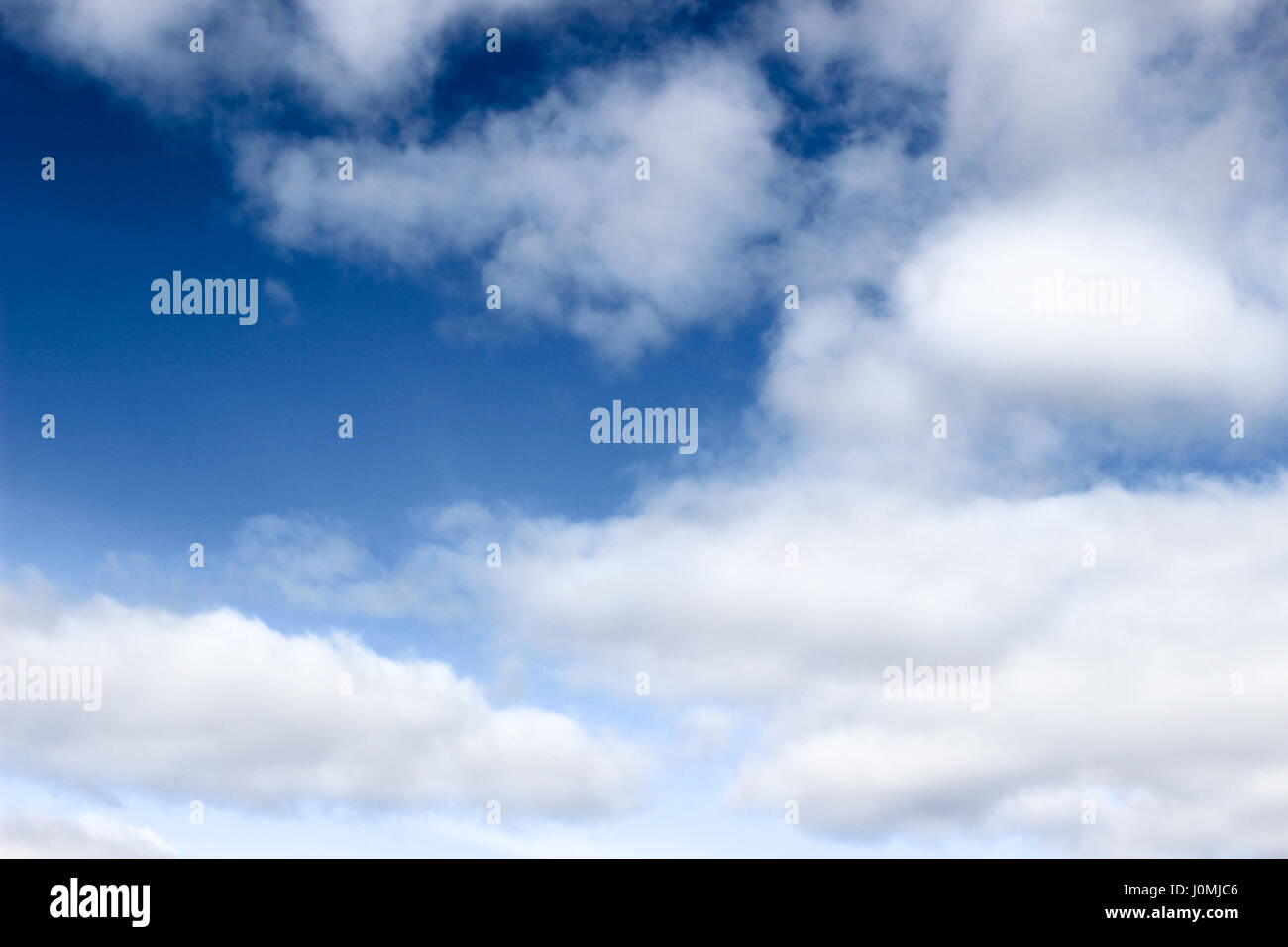 cloud-filled blue sky - Stock Image