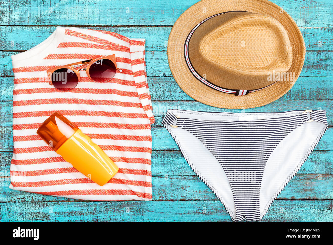 Top view of straw hat, bikini bottom, sunglasses and sunscreen on wooden table, summer concept - Stock Image