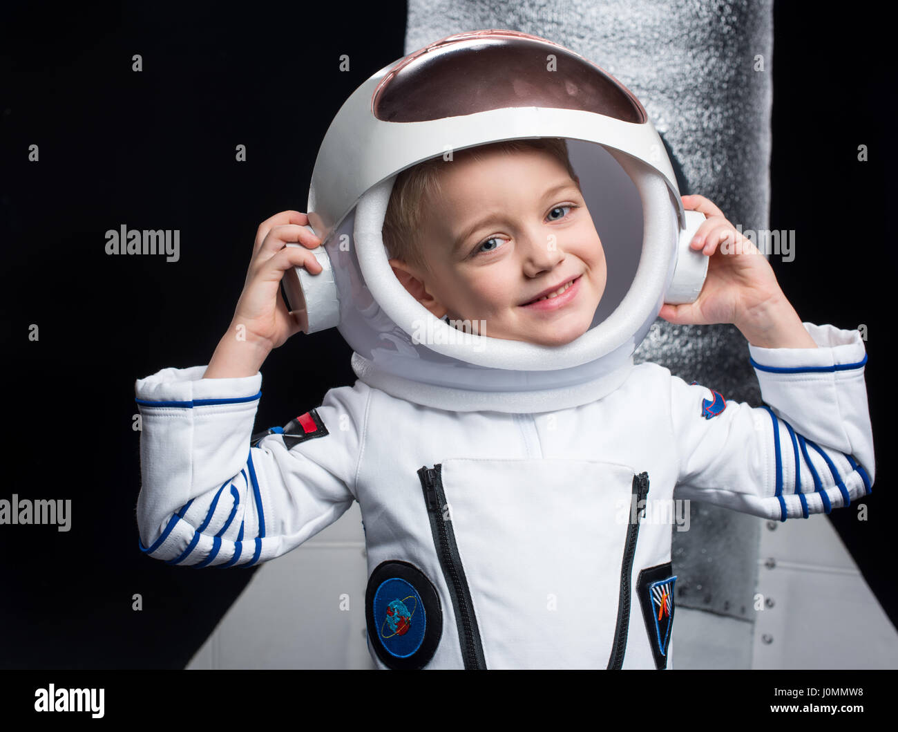 Little boy astronaut in space suit adjusting helmet and ...