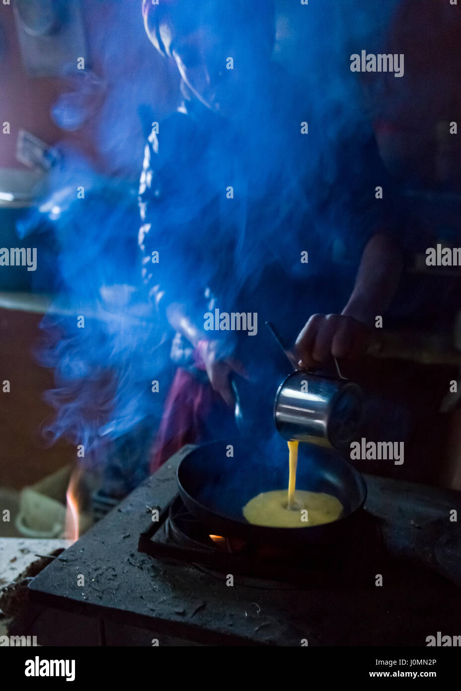 A woman cooking an omelette in a trekkers lodge in the Nepal Himalaya. Photo © robertvansluis.com - Stock Image