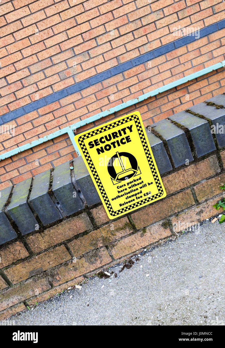 A yellow warning sign saying Cars parked here without authorisation will be clamped, release fee £50 - Stock Image