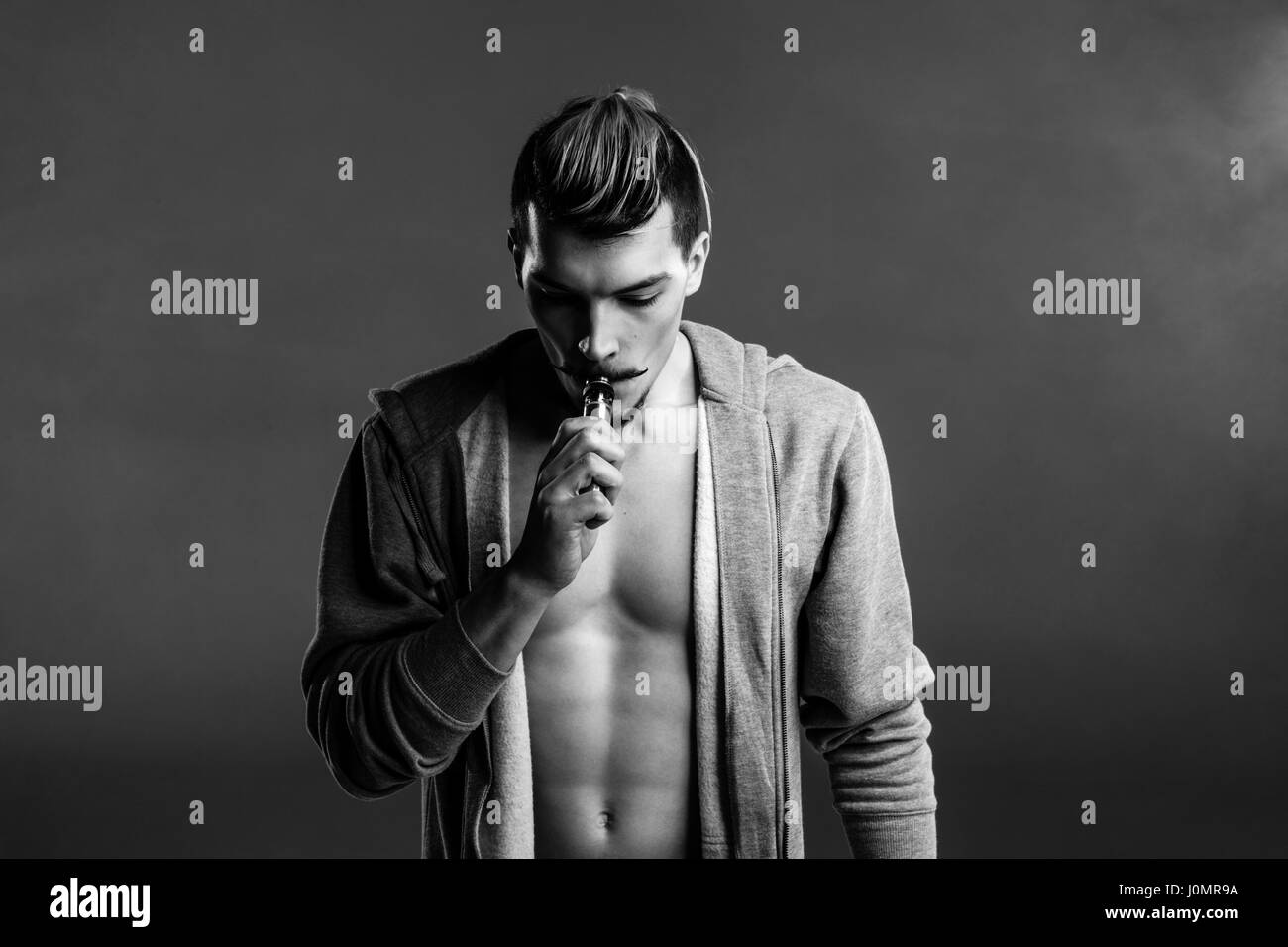 Black and white photo of young handsome man holding electronic cigarette and vaping - Stock Image