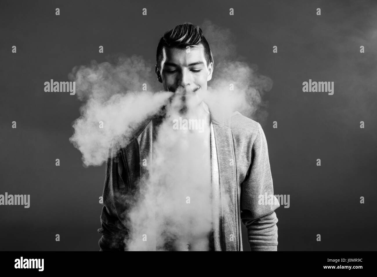 Black and white photo of young handsome man vaping and blowing smoke - Stock Image