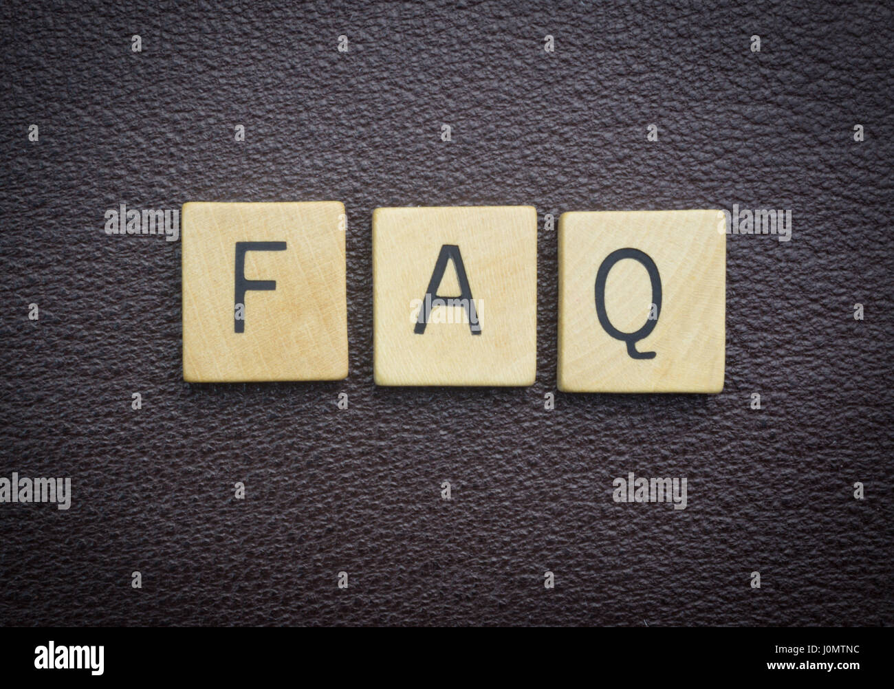 FAQ word concept wood pieces on brown leather - Stock Image