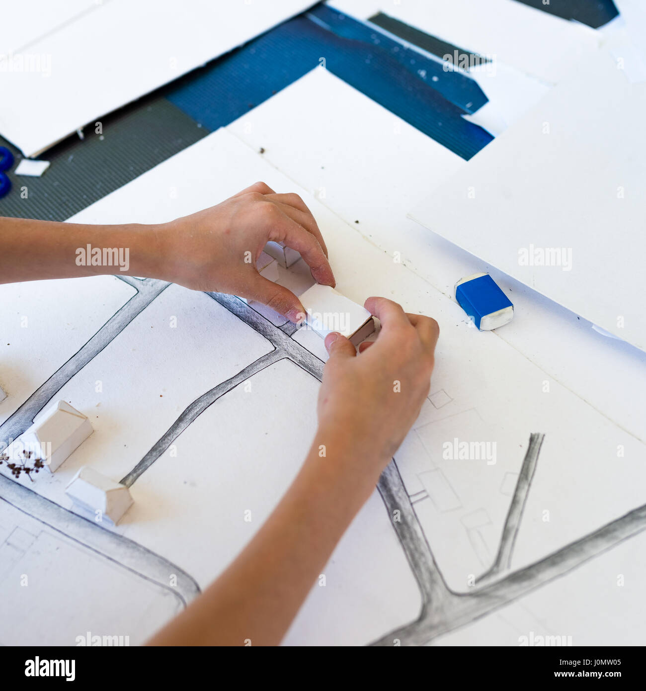 Young girl learning on the course of architectural design for children - preparing architectural model Stock Photo