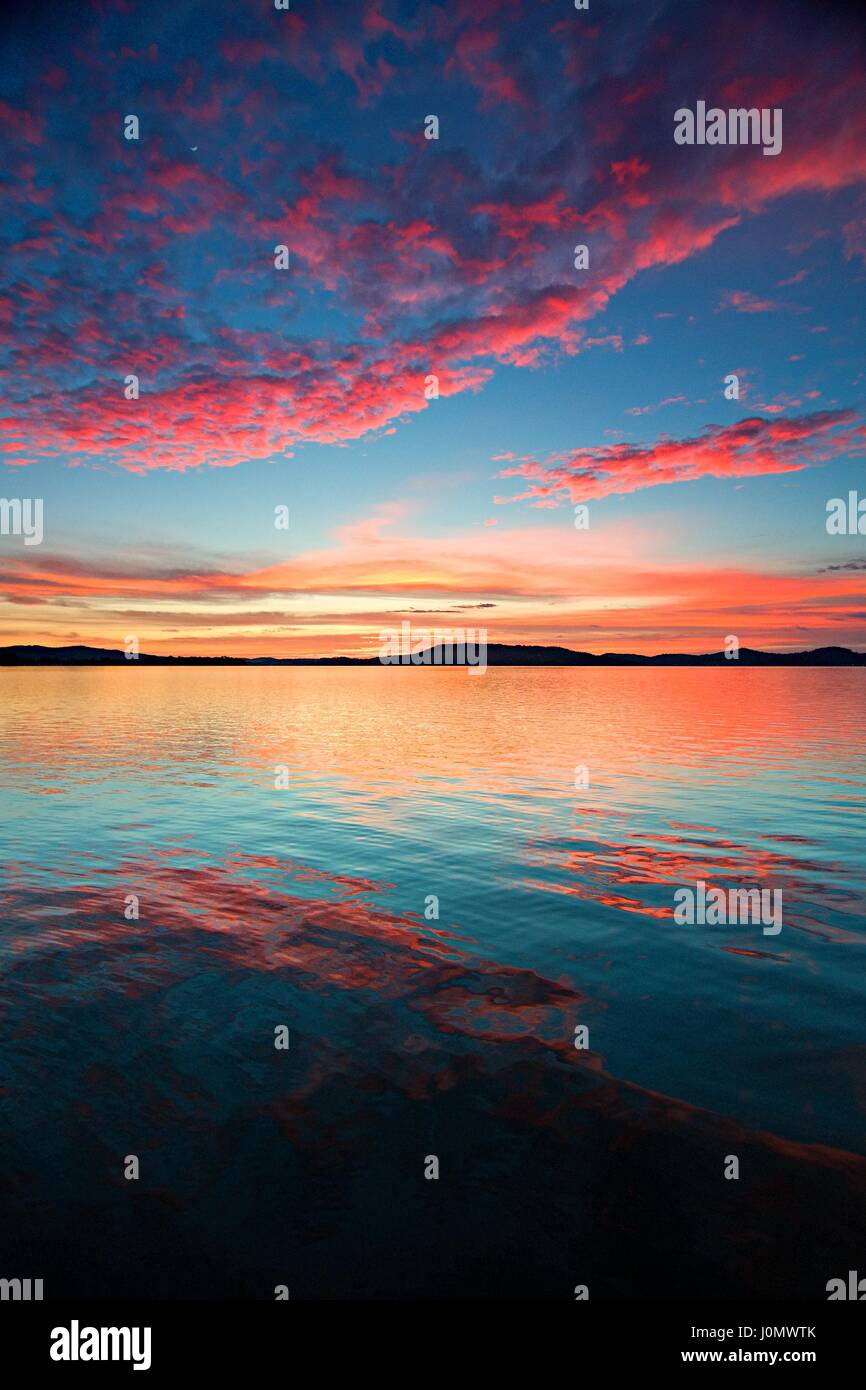 Vivid crimson sunrise with clear water reflections. Captured in New South Wales, Australia. - Stock Image