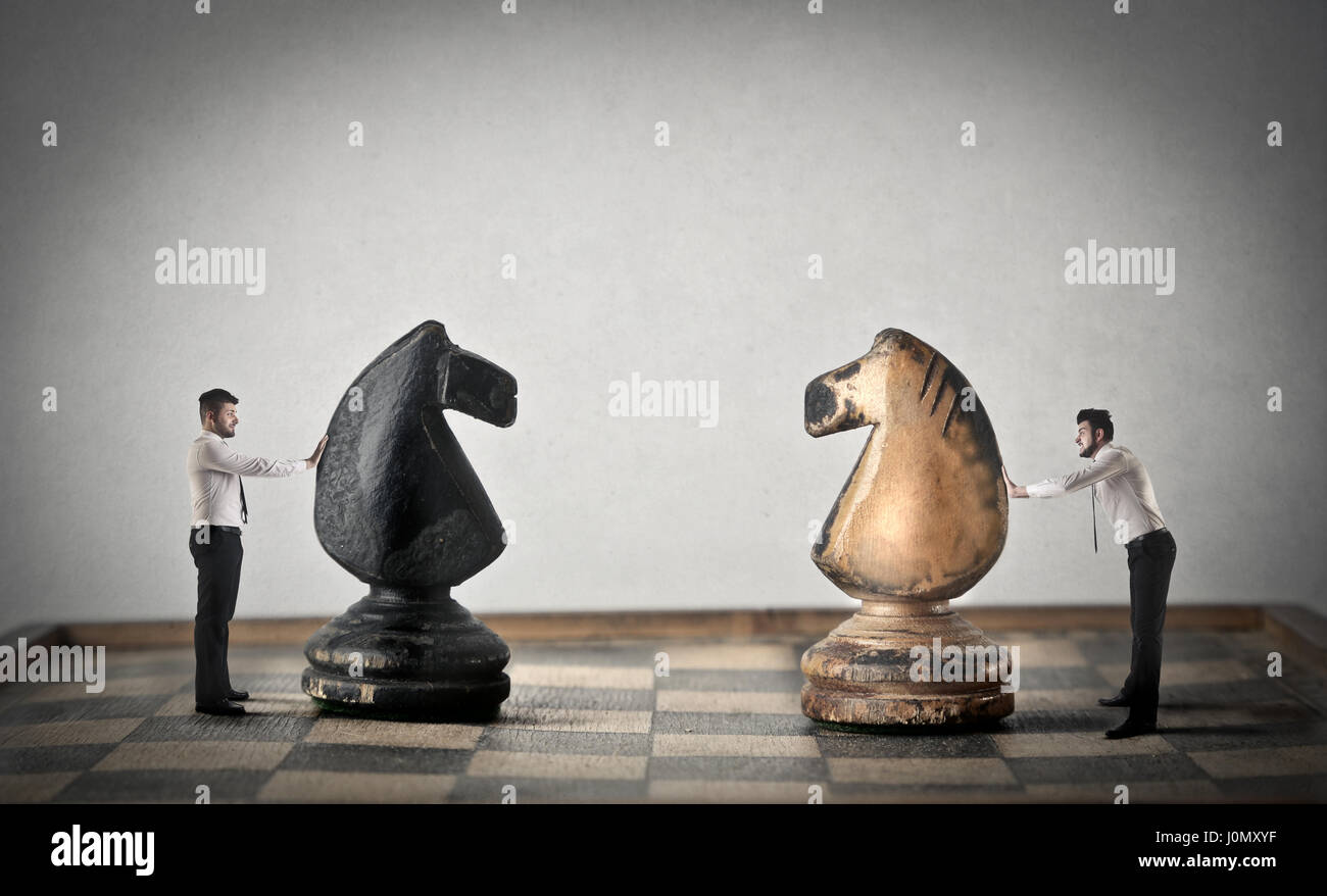 2 businessmen playing with huge chess - Stock Image