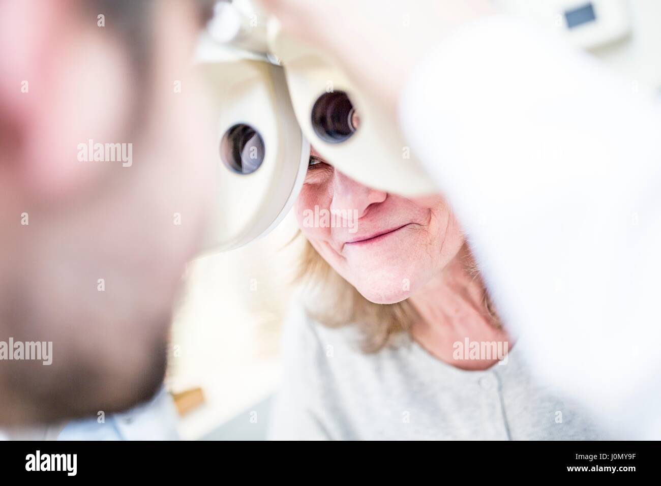 Optometrist performing eye test of senior woman with phoropter in optometrist's shop. Stock Photo