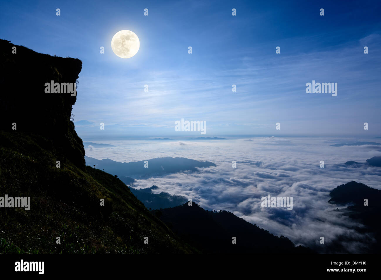 Beautiful Landscape Nature, Full Moon With Bright White Light Over The  Clouds And Fog In The Dark Blue Sky At Night On The Peak Mountain In Winter