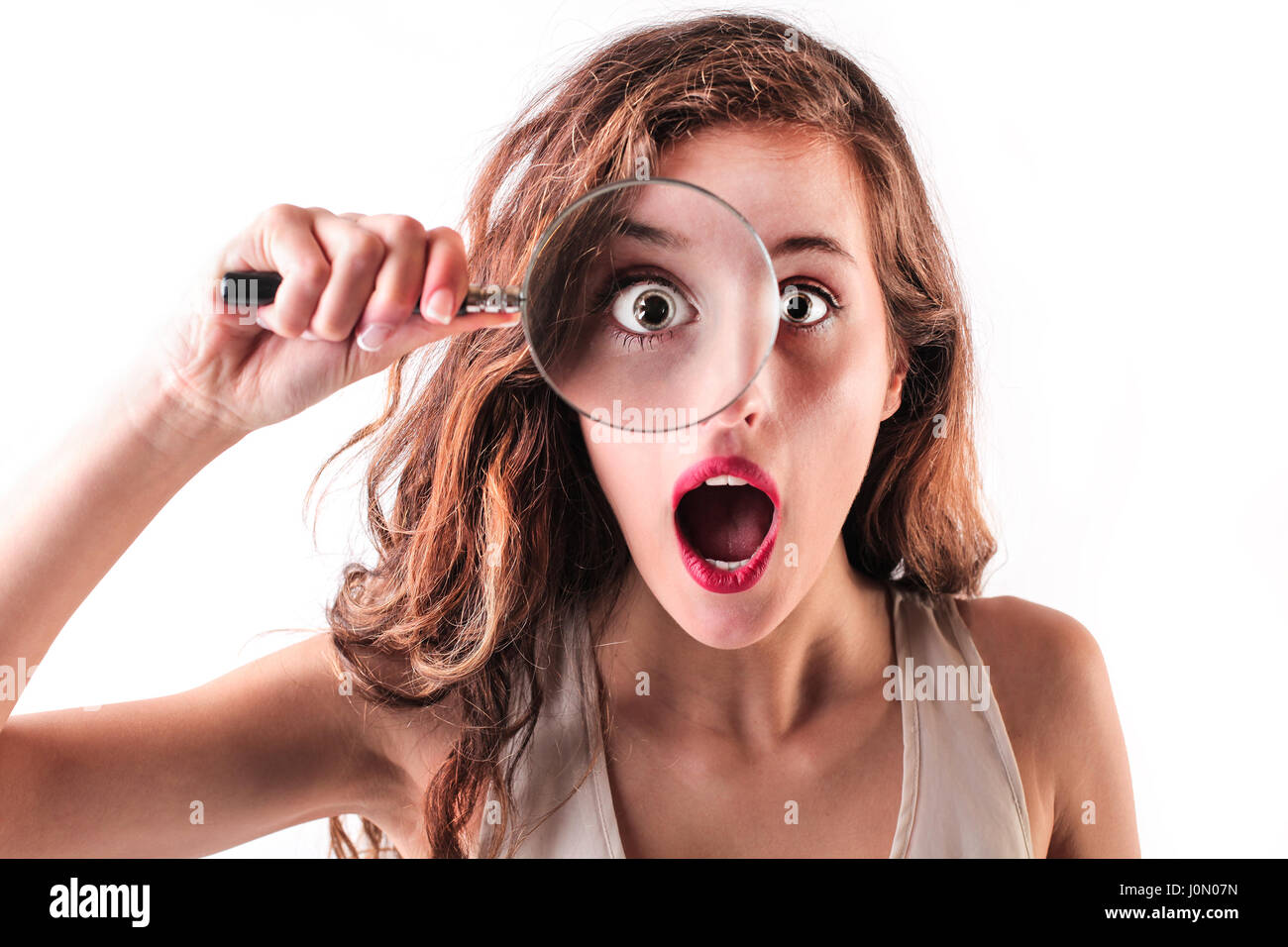 Brunette woman with magnifying glass - Stock Image