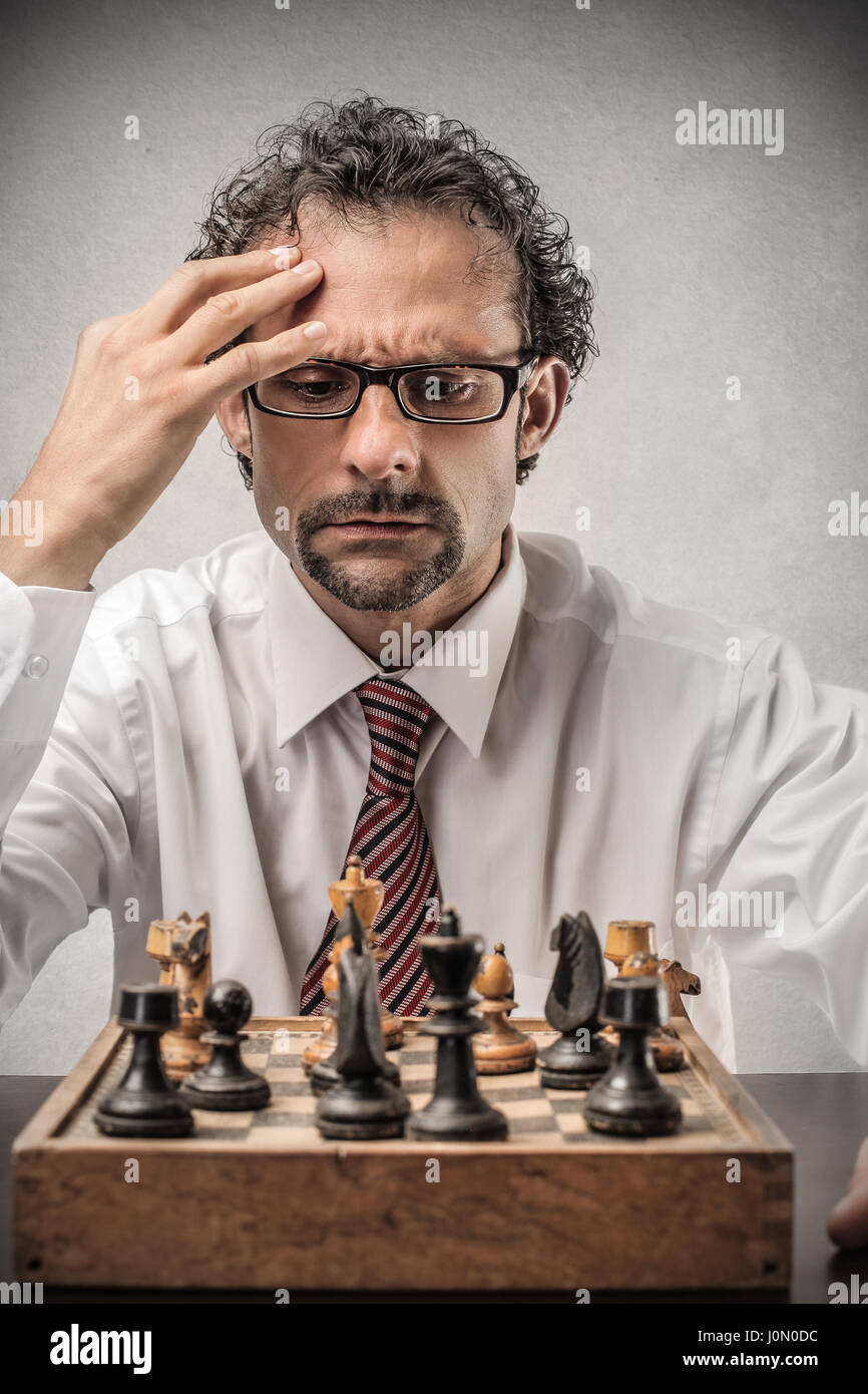 Businessman playing chess - Stock Image
