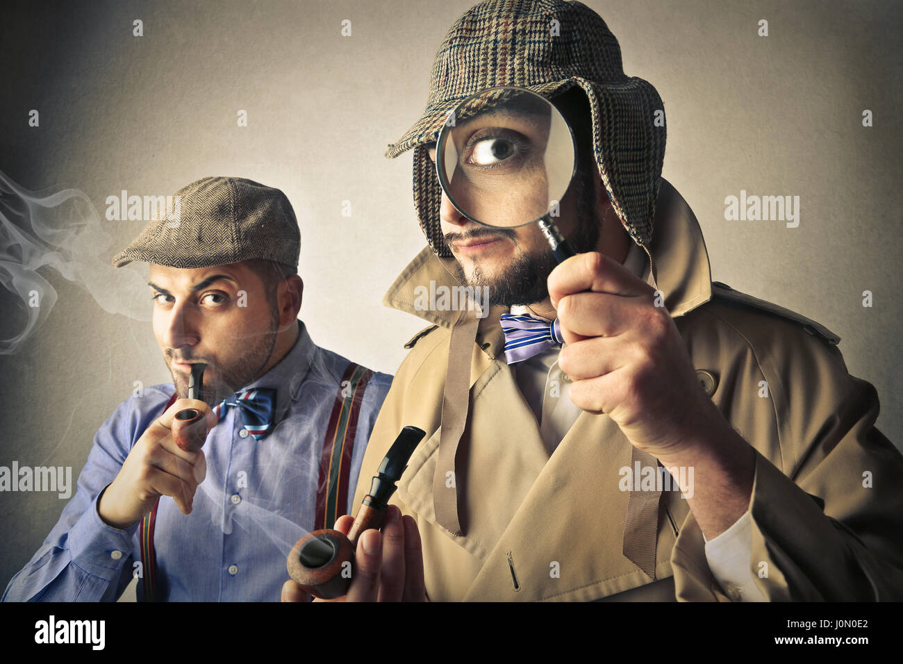 Investigator with magnifying glass and partner - Stock Image