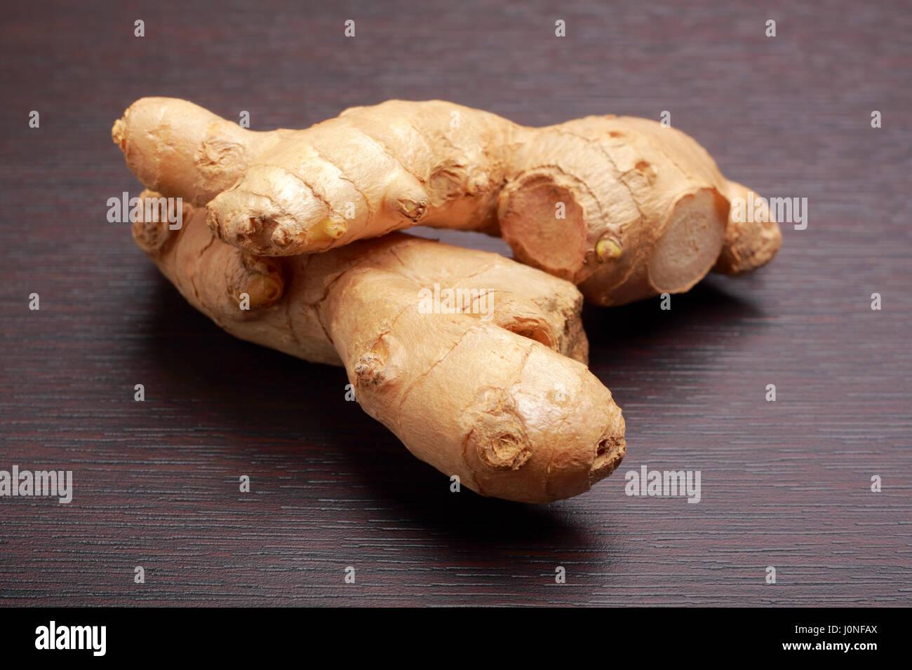 Ginger root (rhizome) lying on dark board - Stock Image