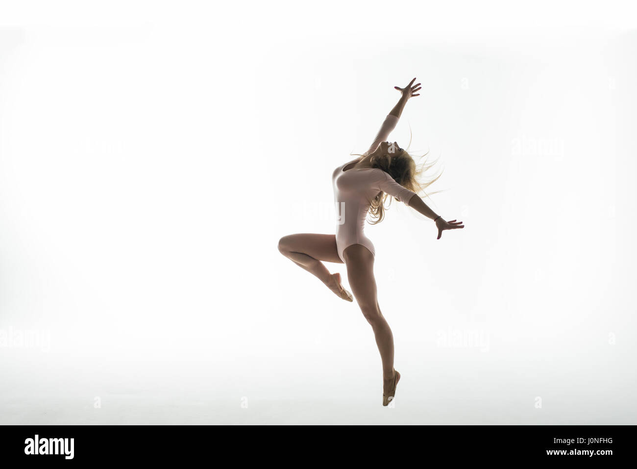 Young slim gymnast in studio on white - Stock Image