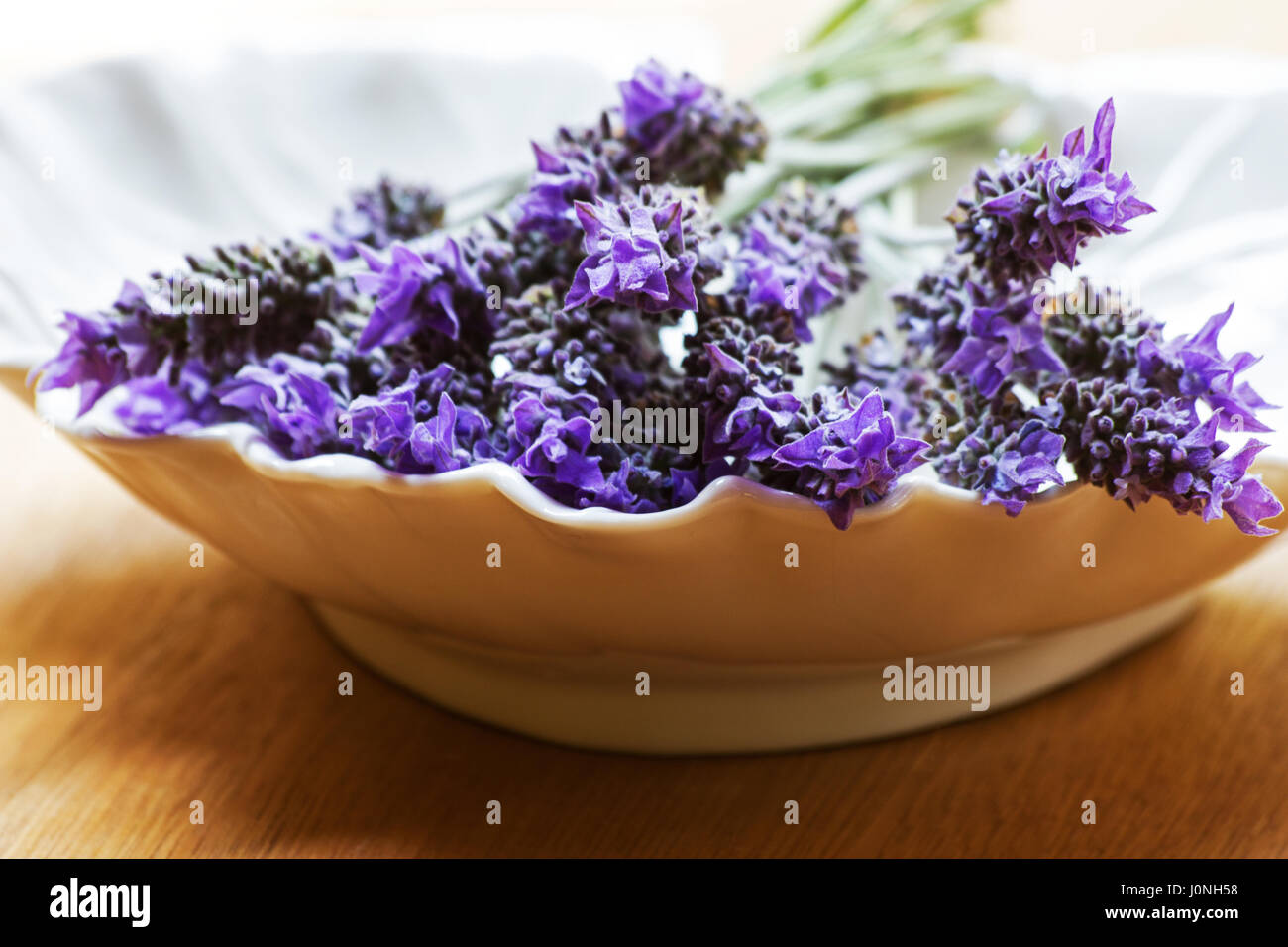 Lavender sprigs in a bowl on a table - Stock Image