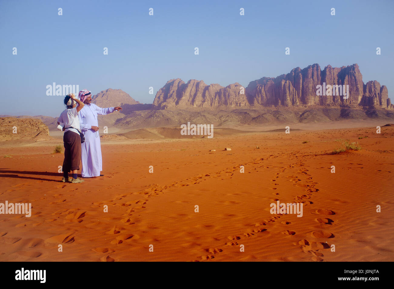 reputable site 29361 ad970 Beduin illustrating rocks formation to a female tourist ...