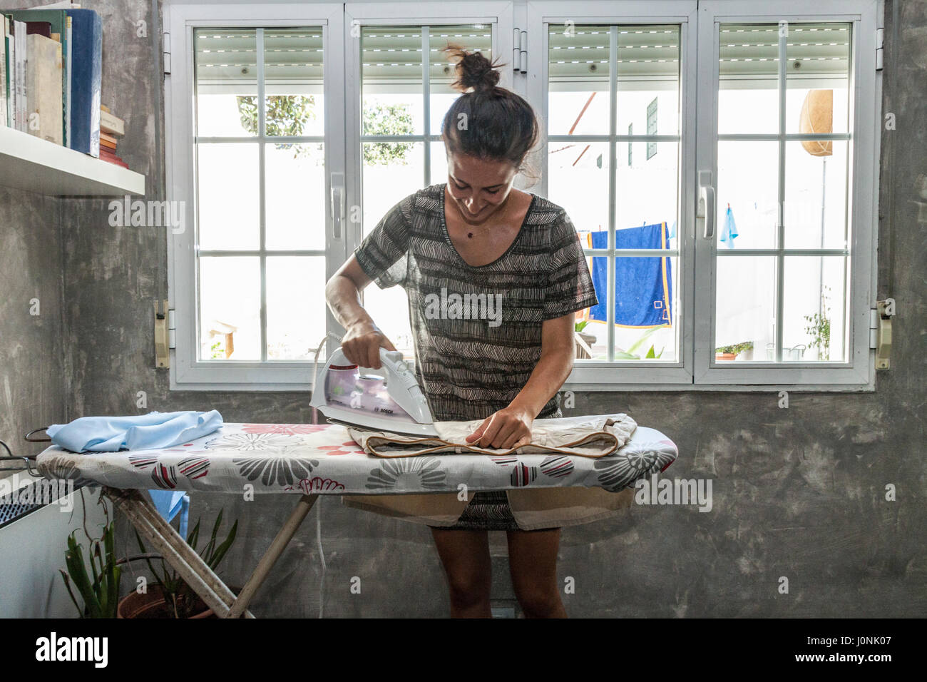 Home chores. One beautiful young woman ironing clothes at home, confortly dressed, hair tied up in a bun. Stock Photo