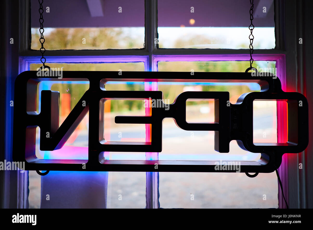 Lit up neon multicoloured Open sign hung in diner window seen from reverse looking outward. - Stock Image