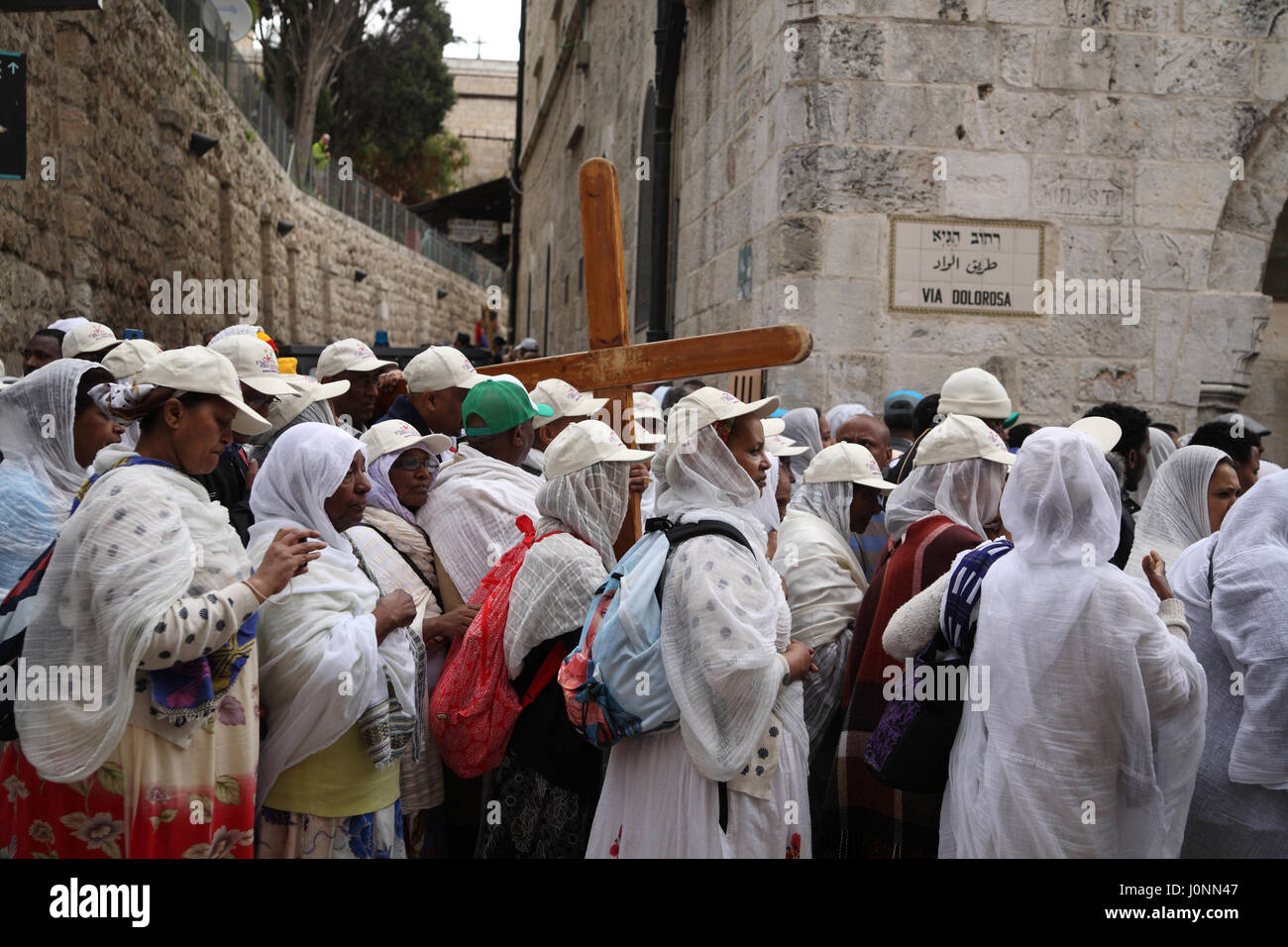 A Good Friday Procession on the Via Dolorosa, Ethiopian Christian pilgrims, carry a simple wooden Cross. - Stock Image
