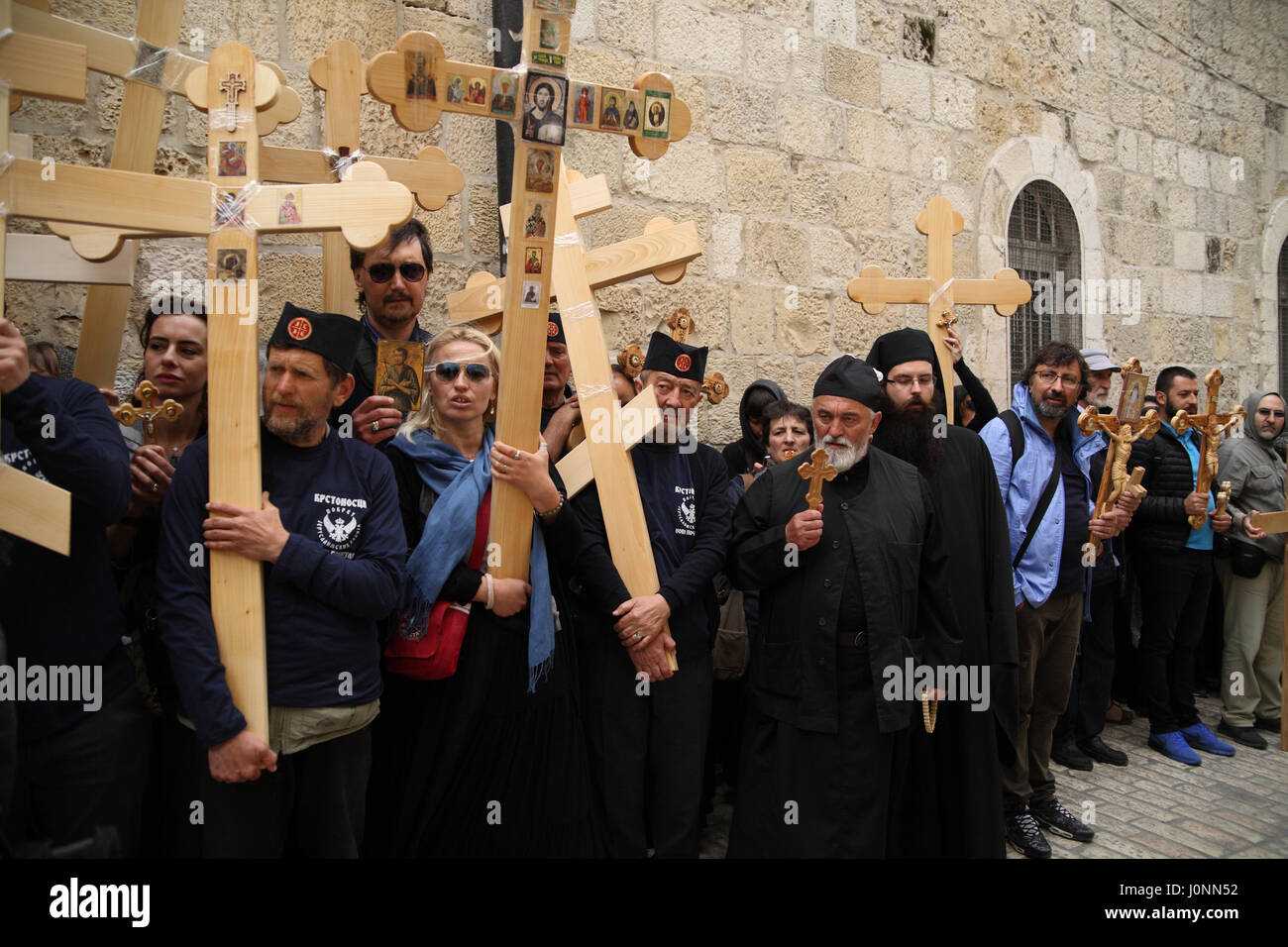 Serbian pilgrims wait against the wall of the Via Dolorosa alley with their wooden ornamented Crosses before they - Stock Image