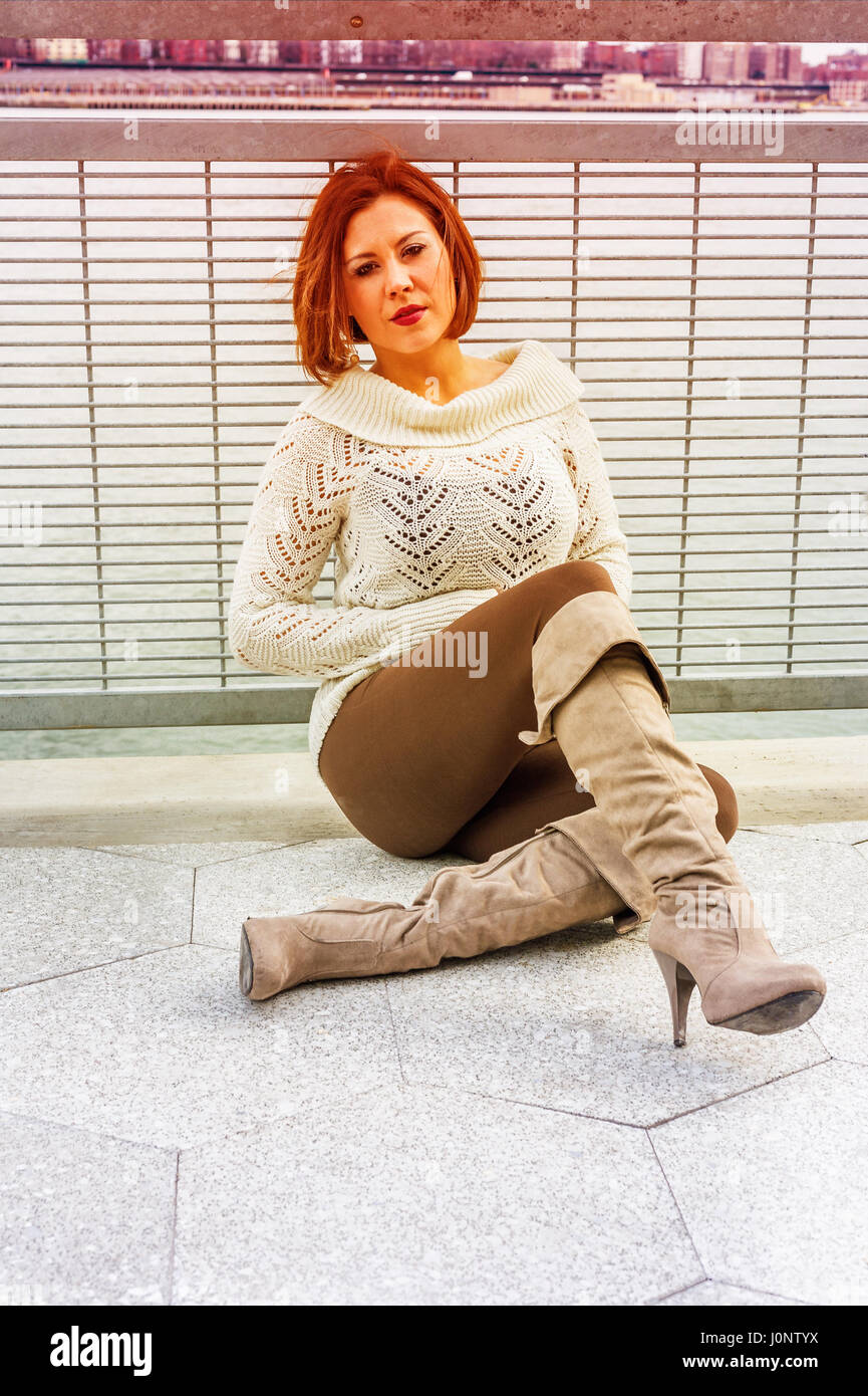 Unhappy American Woman thinking outside, wearing white knit sweater, brown pants, long boots, sitting by railing - Stock Image
