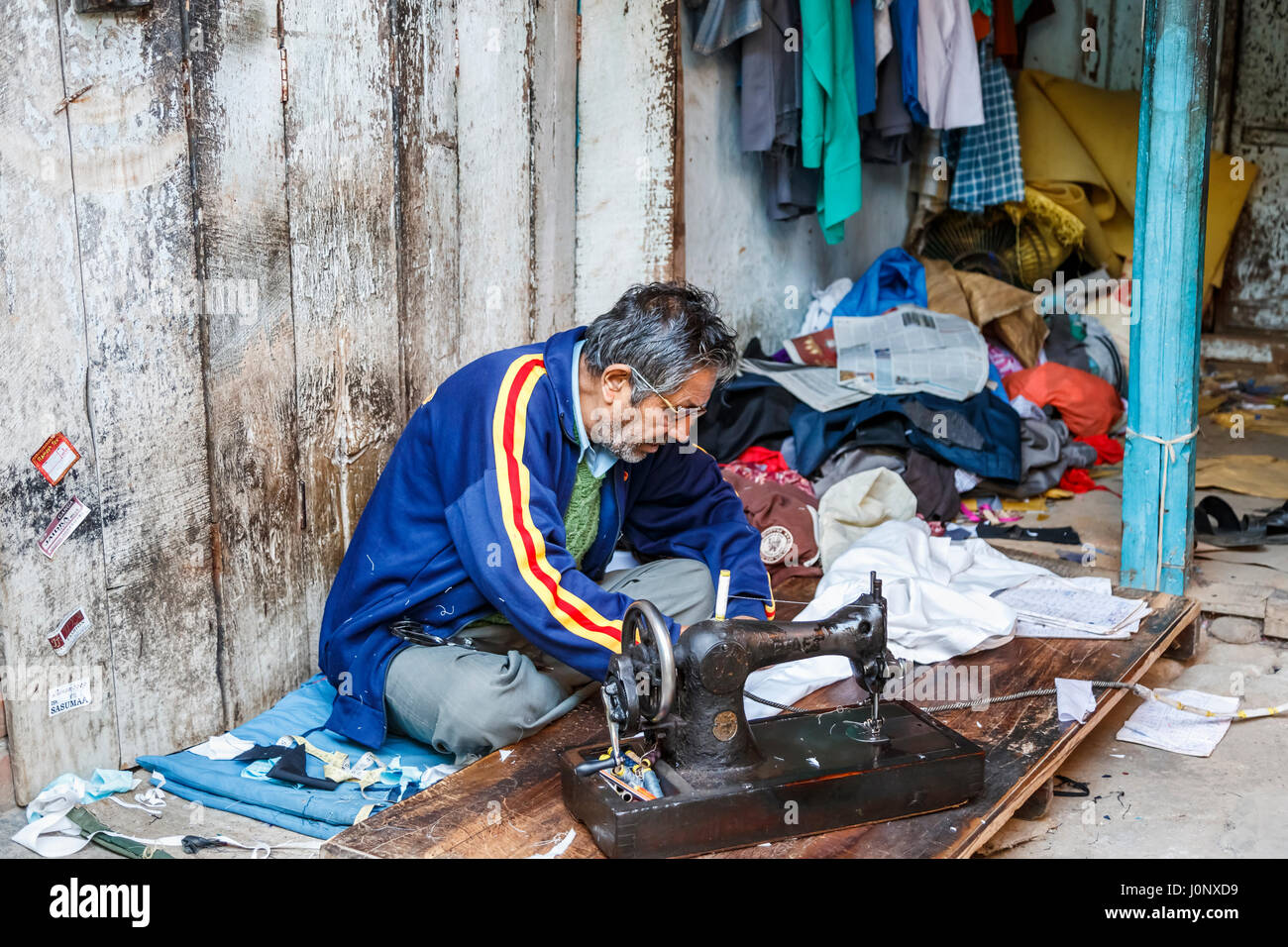 Local Indian man working as a tailor using an old fashioned sewing machine at a roadside shop in Pragpur heritage - Stock Image