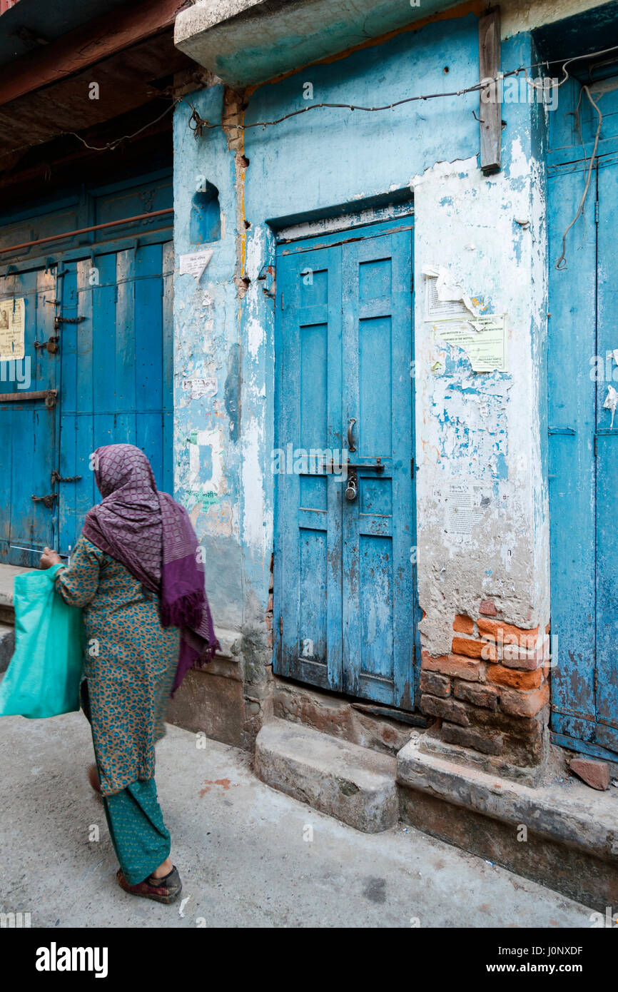 Local Indian woman walking past a blue wooden door in a street in Pragpur heritage village in Kagra district, Himachal - Stock Image