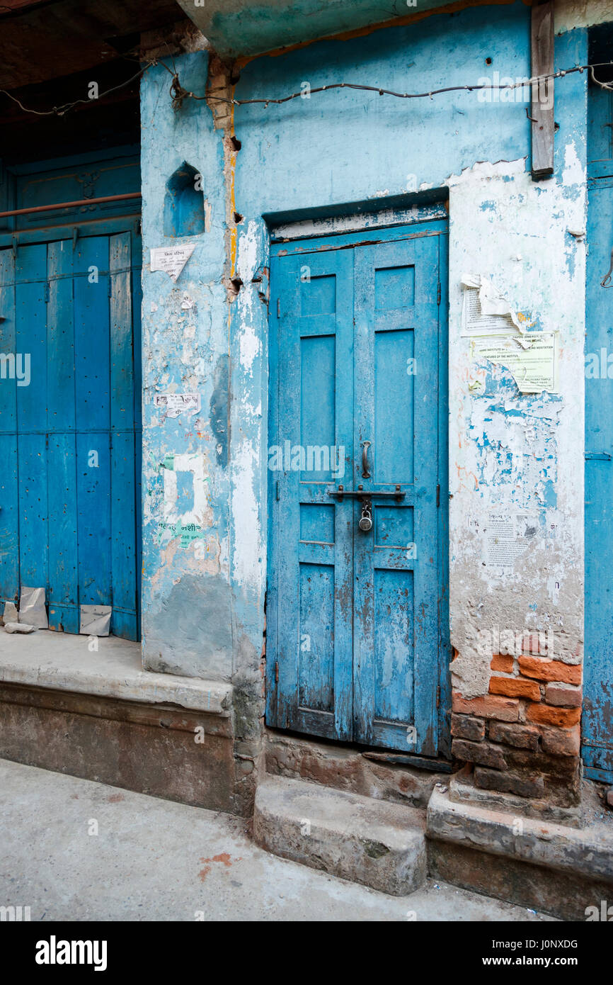 Blue wooden door in a building with crumbling plaster and peeling paint in Pragpur, a heritage village in Kagra - Stock Image