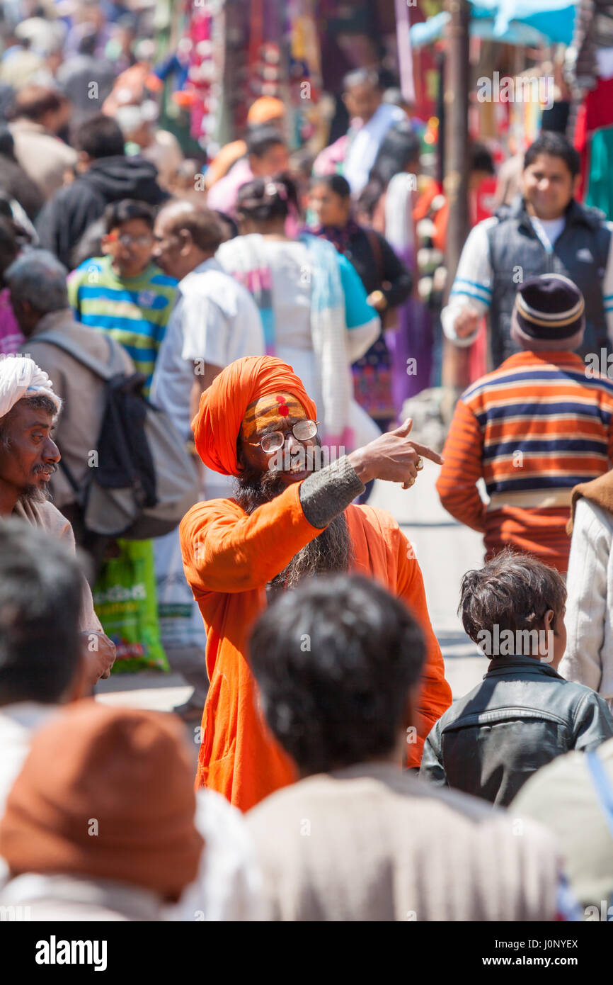 BADRINATH  INDIA, JUNE 5th - A sadhu amongst pilgrims on the streets near the temple of Badarinath in North India - Stock Image