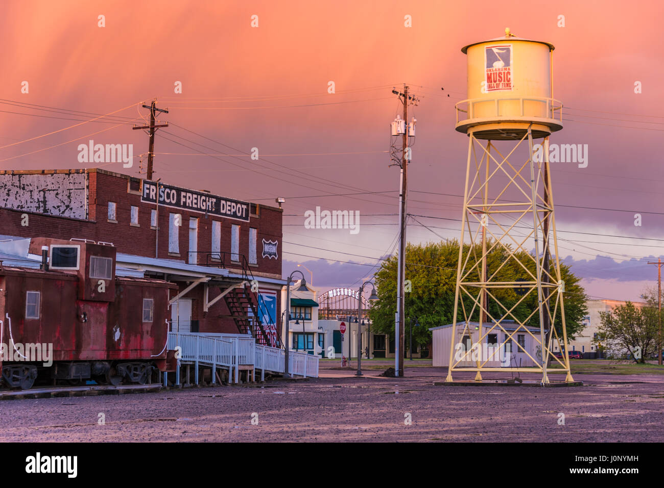 The Oklahoma Music Hall of Fame and iconic water tower at the Frisco Freight Depot under a colorful sunset sky in Muskogee, Oklahoma, USA. Stock Photo