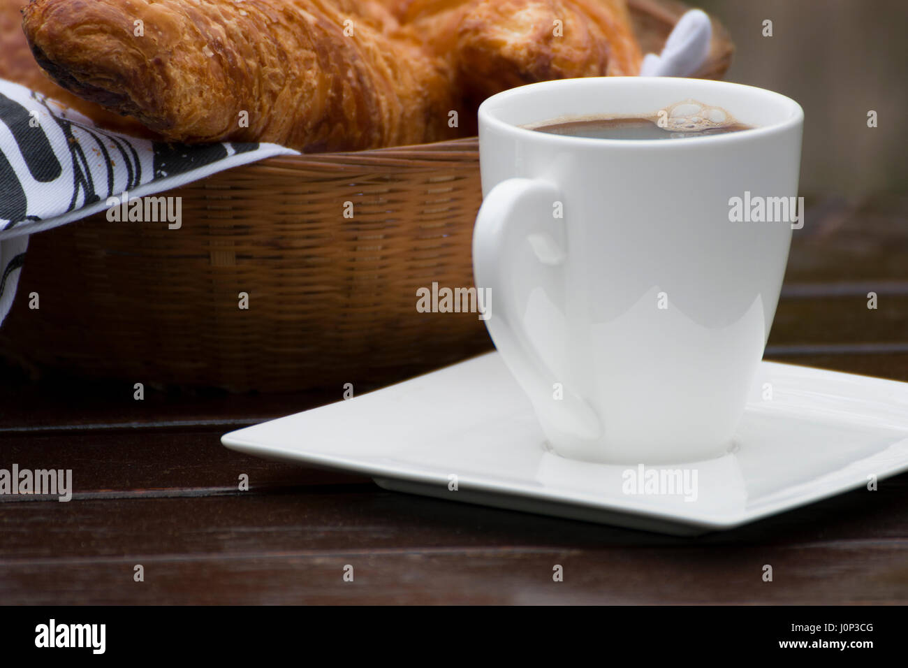 A cup of coffee near a basket with french croissants - Stock Image