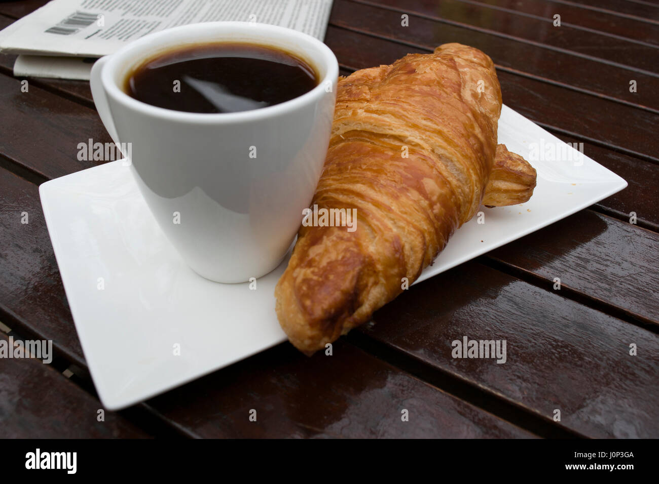 A cup of black coffee and a French croissant, a newspaper on a wooden table, outside. - Stock Image
