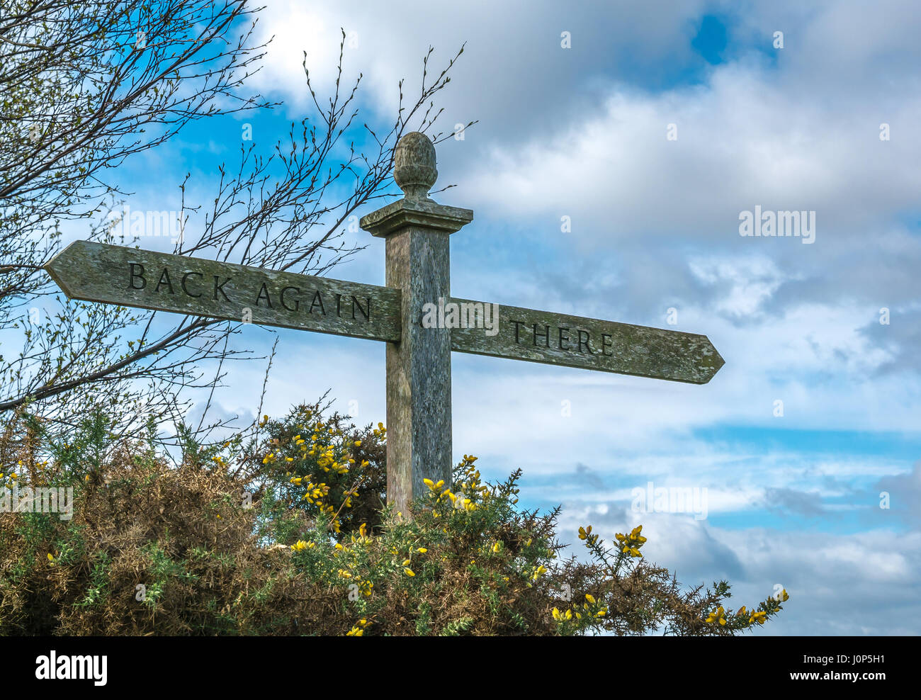 Unusual humorous wooden sign pointing in opposite directions with subtitle from The Hobbit, There and Back Again, - Stock Image