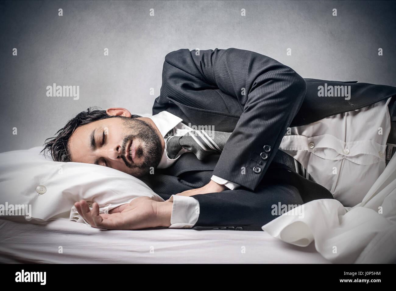 Businessman sleeping on bed - Stock Image